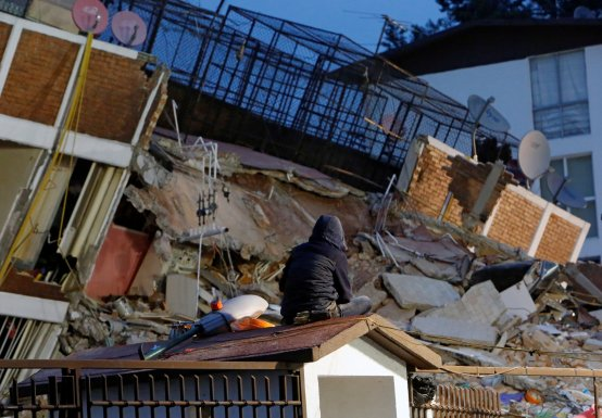 A person sits on the roof of a little house while looking at the rubble of a collapsed building after an earthquake hit Mexico City, Mexico September 20, 2017. REUTERS/Ginnette Riquelme